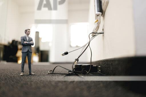 Businessman figurine standing in office, looking at disconnected cables