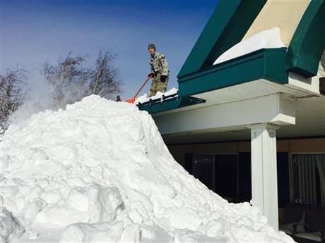 In this photo taken on Wednesday, Nov. 19, 2014, and released by the New York National Guard, an airman with the New York Air National Guard shovels snow off the roof of the Eden Heights Assisted Living Facility in West Seneca, N.Y.