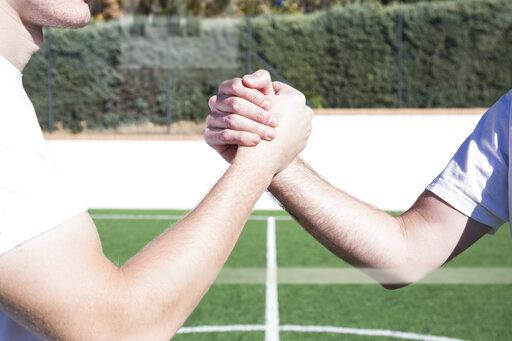 Close-up of two football players shaking hands on football field