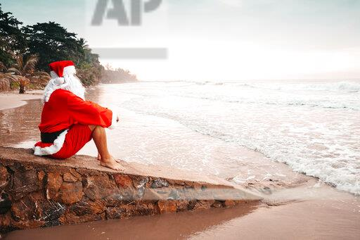 Thailand, man dressed up as Santa Claus sitting on a wall on the beach at sunset