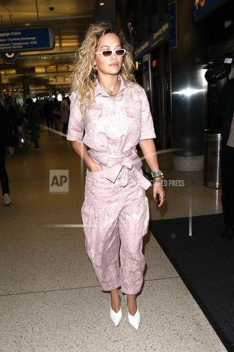Rita Ora looks stunning as she's seen arriving at LAX Airport in a pink jump suit.