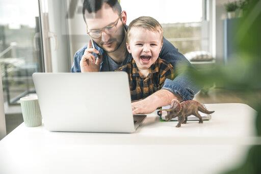 Father working at table in home office with son sitting on his lap