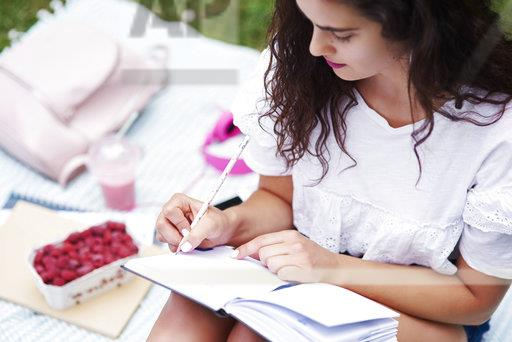 Young woman sitting on blanket on a meadow writing in notebook