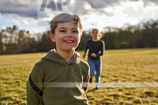 Portrait of happy boy with sister on a meadow