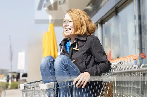 Portrait of laughing woman sitting in shopping cart in front of supermarket