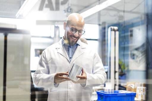 Smiling technician wearing lab coat examining workpiece