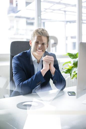Portrait of confident young businessman sitting at desk in office
