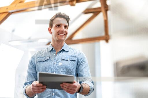 Portrait of smiling young businessman using tablet in office