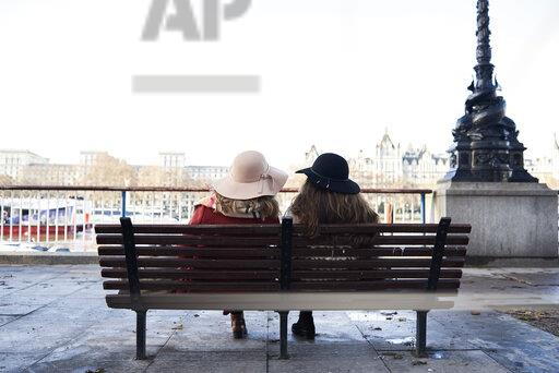UK, London, rear view of two women sitting on a bench at River Thames promenade