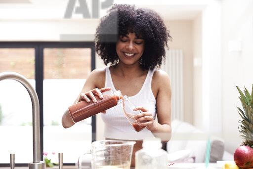 Smiling young woman preparing healthy smoothie in kitchen