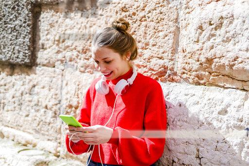 Young woman wearing red pullover, headphones in Verona