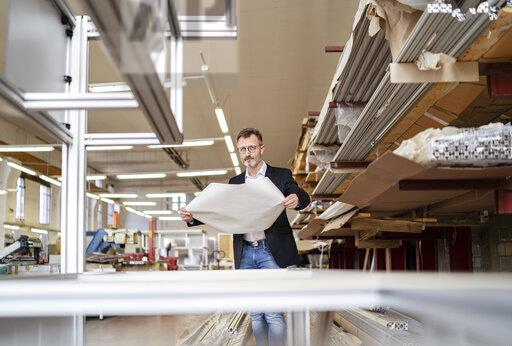 Businessman with plan in factory warehouse