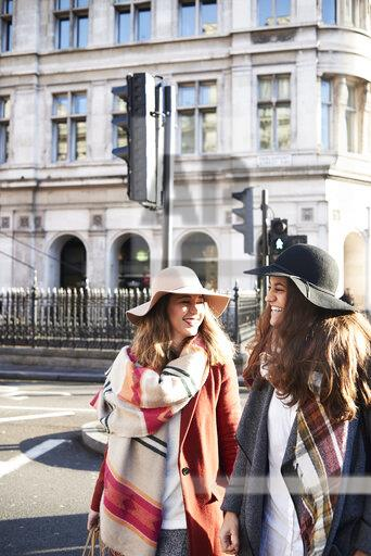 UK, London, two happy women in the city crossing a street