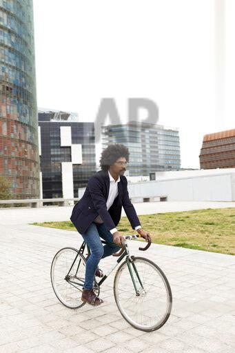 Spain, Barcelona, businessman riding bicycle in the city