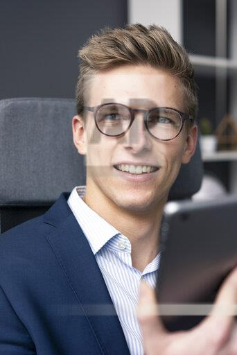 Smiling young businessman sitting on office chair using tablet