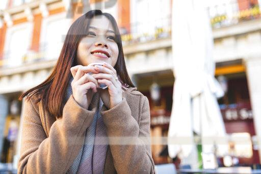 Spain, Madrid, smiling young woman in a cafe at Plaza Mayor