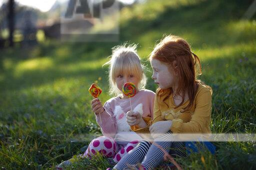 Two sisters sitting in a field holding lollipops