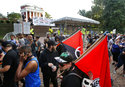 A group of anti-fascist and Black Lives Matter demonstrators march in front of the Rotunda on the campus of the University of Virginia in anticipation of the anniversary of last year's Unite the Right rally in Charlottesville, Va., Saturday, Aug. 11, 2018. (AP Photo/Steve Helber)