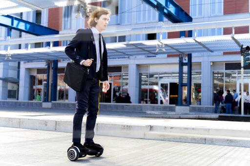 Italy, Florence, young businessman riding hoverboard in the city