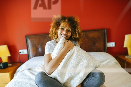 Portrait of happy young woman with curly hair sitting on bed at home holding pillow