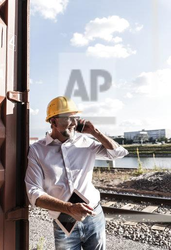 Businessman at cargo harbour, wearing safety helmet, using smartphone and digital tablet