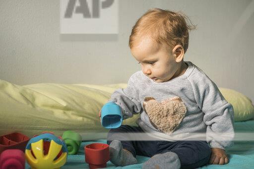 Baby girl sitting on bed playing with plastic toy