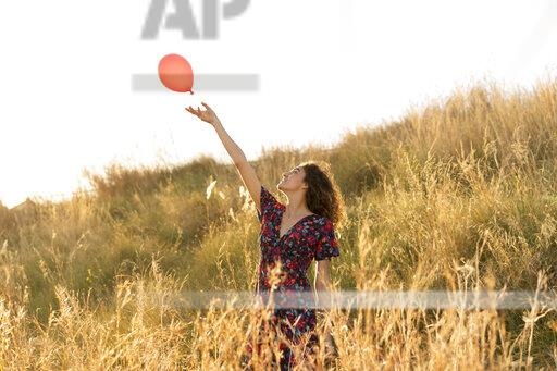Happy young woman standing in summer meadow, letting go of a red balloon