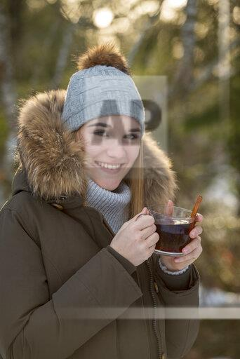 Portrait of smiling young woman drinking tea in winter