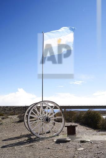 Argentina, Patagonia, Argentinan flag on wooden wheels against blue sky