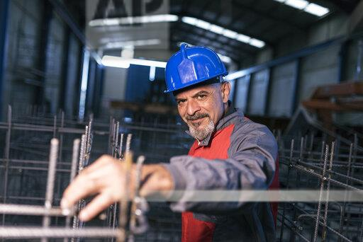 Portrait of confident worker wearing hard hat in factory checking rebar