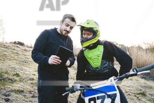 Motocross talking to coach with tablet