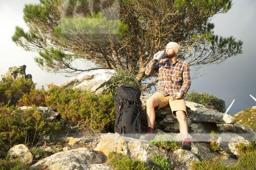 Spain, Andalusia, Tarifa, man on a hiking trip having a break drinking from flask