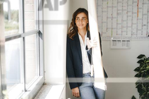 Woman standing in office, looking out of window