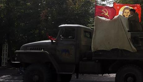 A Pro-Russian rebels truck arranged with a communists flag, left and a flag with an Orthodox style icon depicting Jesus Christ is driven in a parade in the town of Luhansk, eastern Ukraine, Sunday, Sept. 14, 2014. Some semblance of normality is returning to parts of eastern Ukraine after a cease-fire agreement sealed between Ukrainian government forces and separatist rebels earlier this month, although exchanges of rocket fire remain a constant in some areas. (AP Photo/Darko Vojinovic)