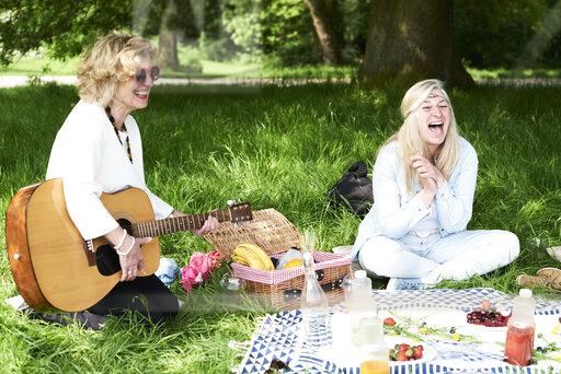 Women with guitar having fun at a picnic in park