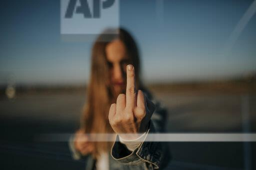 Close-up of young woman outdoors giving the finger
