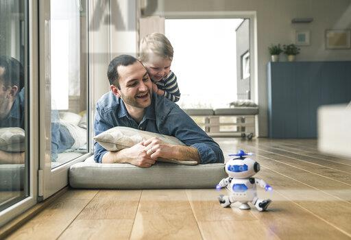 Excited father and son lying on a mattress at home watching a toy robot