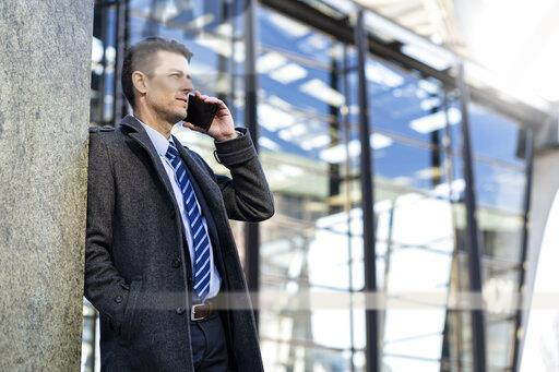 Businessman on cell phone leaning against a wall