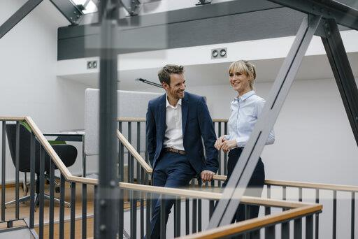 Businessman and woman standing in office building, discussing