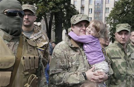A father, a volunteer, holds his little daughter as relatives and friends say good-buy to volunteers before they were sent to the eastern part of Ukraine to join the ranks of special battalion unit fighting against pro-Russian separatists, in Kiev, Ukraine, Tuesday, Aug. 26, 2014. It was the second straight day that attacks were reported in the vicinity of Novoazovsk, which is in eastern Ukraine's separatist Donetsk region but previously had seen little fighting between Ukrainian forces and pro-Russian rebels. (AP Photo/Efrem Lukatsky)