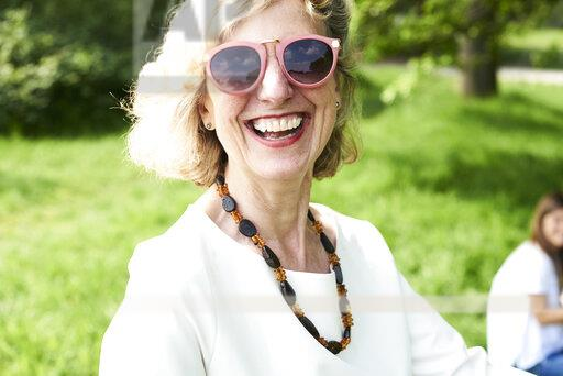 Portrait of happy senior woman wearing sunglasses in park