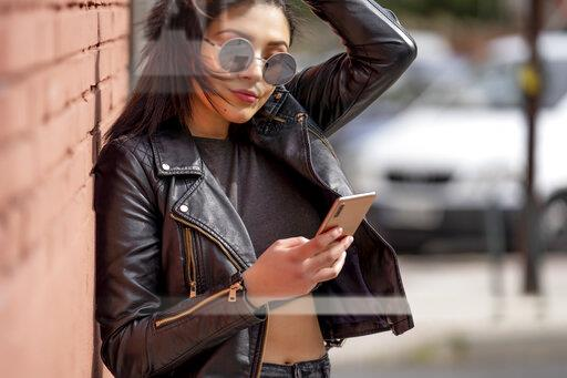 Portrait of young woman wearing sunglasses and black leather jacket looking at smartphone