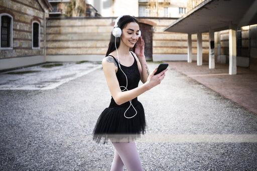 Italy, Verona, smiling woman in ballet dress with cell phone and headphones