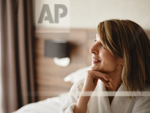 Thoughtful smiling blond woman looking away while sitting in hotel room