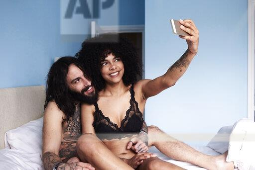 Happy affectionate young couple taking a selfie in bed