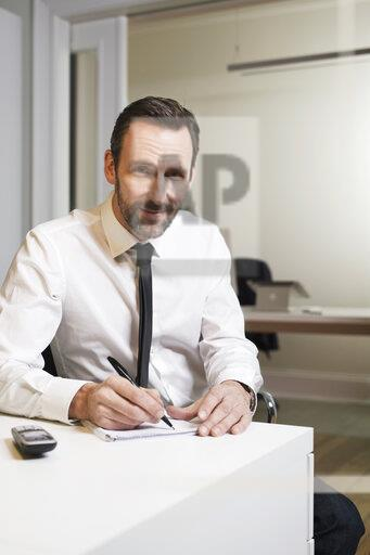 Portrait of confident businessman sitting at desk in office taking notes