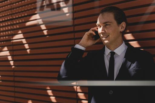 Smiling young businessman on smartphone outdoor