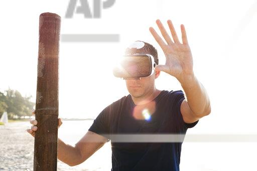 Man with wood pole wearing VR glasses on the beach