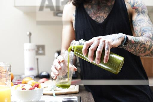 Tattooed young man pouring in healthy smoothie in kitchen