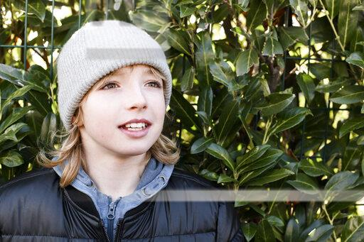 Portrait of boy wearing wooly hat at a hedge